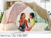 Купить «girls playing with torch in kids tent at home», фото № 32130987, снято 18 февраля 2018 г. (c) Syda Productions / Фотобанк Лори