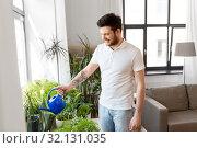 Купить «man watering houseplants at home», фото № 32131035, снято 22 мая 2019 г. (c) Syda Productions / Фотобанк Лори