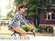 Купить «young hipster man with bag riding fixed gear bike», фото № 32131075, снято 15 июня 2016 г. (c) Syda Productions / Фотобанк Лори