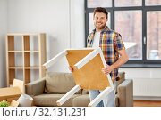 Купить «happy man with table moving to new home», фото № 32131231, снято 22 мая 2019 г. (c) Syda Productions / Фотобанк Лори