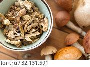Купить «dried mushrooms in bowl on wooden background», фото № 32131591, снято 13 сентября 2018 г. (c) Syda Productions / Фотобанк Лори