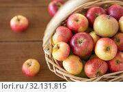 ripe apples in wicker basket on wooden table. Стоковое фото, фотограф Syda Productions / Фотобанк Лори