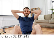 smiling man making abdominal exercises at home. Стоковое фото, фотограф Syda Productions / Фотобанк Лори