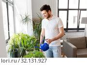 Купить «man watering houseplants at home», фото № 32131927, снято 22 мая 2019 г. (c) Syda Productions / Фотобанк Лори