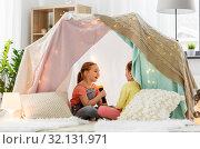 Купить «girls playing with torch in kids tent at home», фото № 32131971, снято 18 февраля 2018 г. (c) Syda Productions / Фотобанк Лори