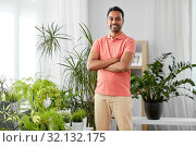 smiling indian man with houseplants at home. Стоковое фото, фотограф Syda Productions / Фотобанк Лори
