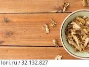 Купить «dried mushrooms in bowl on wooden background», фото № 32132827, снято 13 сентября 2018 г. (c) Syda Productions / Фотобанк Лори