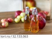 Купить «bottles of apple juice or vinegar on wooden table», фото № 32133063, снято 23 августа 2018 г. (c) Syda Productions / Фотобанк Лори