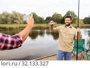 Купить «friend photographing fisherman with fish at lake», фото № 32133327, снято 8 сентября 2018 г. (c) Syda Productions / Фотобанк Лори