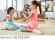 Купить «happy little sisters playing clapping game at home», фото № 32133631, снято 31 марта 2019 г. (c) Syda Productions / Фотобанк Лори
