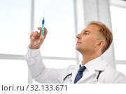 smiling doctor with syringe at hospital. Стоковое фото, фотограф Syda Productions / Фотобанк Лори