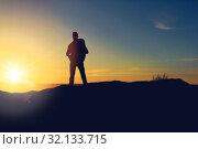 Купить «traveller standing on edge of hill over sunrise», фото № 32133715, снято 31 августа 2014 г. (c) Syda Productions / Фотобанк Лори