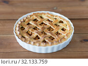 Купить «apple pie in baking mold on wooden table», фото № 32133759, снято 23 августа 2018 г. (c) Syda Productions / Фотобанк Лори