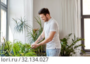 Купить «man cleaning houseplant's leaves at home», фото № 32134027, снято 22 мая 2019 г. (c) Syda Productions / Фотобанк Лори