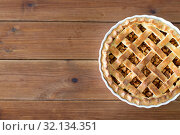 Купить «close up of apple pie in mold on wooden table», фото № 32134351, снято 23 августа 2018 г. (c) Syda Productions / Фотобанк Лори