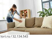 Купить «asian woman arranging sofa cushions at home», фото № 32134543, снято 13 апреля 2019 г. (c) Syda Productions / Фотобанк Лори