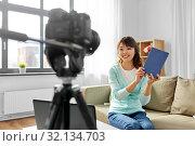 Купить «asian female blogger making video review of book», фото № 32134703, снято 13 апреля 2019 г. (c) Syda Productions / Фотобанк Лори