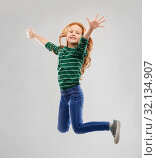 smiling red haired girl in striped shirt jumping. Стоковое фото, фотограф Syda Productions / Фотобанк Лори