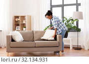Купить «african american woman arranging sofa cushions», фото № 32134931, снято 7 апреля 2019 г. (c) Syda Productions / Фотобанк Лори