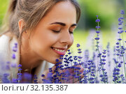 Купить «close up of woman smelling lavender flowers», фото № 32135387, снято 12 июля 2019 г. (c) Syda Productions / Фотобанк Лори