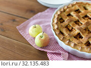 Купить «apple pie in baking mold on wooden table», фото № 32135483, снято 23 августа 2018 г. (c) Syda Productions / Фотобанк Лори