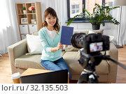 Купить «asian female blogger making video review of book», фото № 32135503, снято 13 апреля 2019 г. (c) Syda Productions / Фотобанк Лори