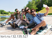 Купить «friends with drinks taking selfie by smartphone», фото № 32135527, снято 15 июня 2019 г. (c) Syda Productions / Фотобанк Лори