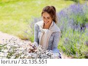 Купить «young woman with flowers at summer garden», фото № 32135551, снято 12 июля 2019 г. (c) Syda Productions / Фотобанк Лори