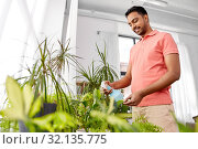 Купить «man spraying houseplant with water at home», фото № 32135775, снято 19 мая 2019 г. (c) Syda Productions / Фотобанк Лори
