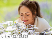 Купить «close up of woman smelling chamomile flowers», фото № 32135835, снято 12 июля 2019 г. (c) Syda Productions / Фотобанк Лори