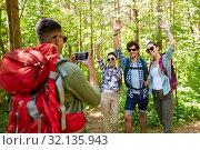 Купить «friends with backpacks being photographed on hike», фото № 32135943, снято 15 июня 2019 г. (c) Syda Productions / Фотобанк Лори