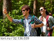 Купить «mixed race couple with backpacks hiking in forest», фото № 32136039, снято 15 июня 2019 г. (c) Syda Productions / Фотобанк Лори