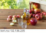 Купить «glasses and bottles of apple juice on wooden table», фото № 32136235, снято 23 августа 2018 г. (c) Syda Productions / Фотобанк Лори