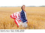happy girl in american flag on cereal field. Стоковое фото, фотограф Syda Productions / Фотобанк Лори