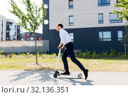 Купить «young businessman riding electric scooter outdoors», фото № 32136351, снято 1 августа 2019 г. (c) Syda Productions / Фотобанк Лори