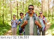 Купить «friends with backpacks on hike in forest», фото № 32136551, снято 15 июня 2019 г. (c) Syda Productions / Фотобанк Лори