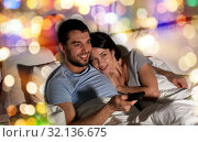 Купить «happy couple watching tv in bed at night at home», фото № 32136675, снято 27 января 2018 г. (c) Syda Productions / Фотобанк Лори