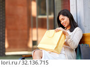 Купить «asian woman with shopping bags on bench in city», фото № 32136715, снято 13 июля 2019 г. (c) Syda Productions / Фотобанк Лори