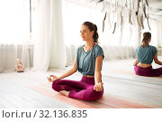 Купить «woman meditating in lotus pose at yoga studio», фото № 32136835, снято 21 июня 2018 г. (c) Syda Productions / Фотобанк Лори
