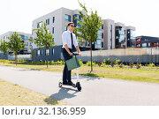 Купить «businessman with shopping bag riding scooter», фото № 32136959, снято 1 августа 2019 г. (c) Syda Productions / Фотобанк Лори
