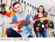 Купить «Female and male rock-n-roll players are deciding on suitable amp», фото № 32140627, снято 14 февраля 2017 г. (c) Яков Филимонов / Фотобанк Лори
