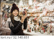Купить «Portrait of young girl choosing Christmas gifts», фото № 32140651, снято 22 декабря 2016 г. (c) Яков Филимонов / Фотобанк Лори