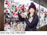 Купить «Positive young woman buying christmas gifts», фото № 32140659, снято 22 декабря 2016 г. (c) Яков Филимонов / Фотобанк Лори