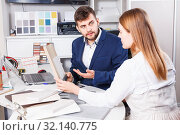 Купить «Competent seller in showroom helping young female client to choose furniture materials for her apartment», фото № 32140775, снято 9 апреля 2018 г. (c) Яков Филимонов / Фотобанк Лори