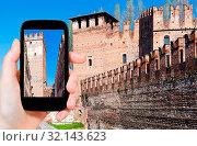 Travel concept - tourist photographs walls of Castelvecchio (Scaliger) Castel in Verona city in Italy on smartphone. Стоковое фото, фотограф Zoonar.com/Valery Voennyy / easy Fotostock / Фотобанк Лори
