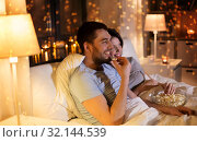 Купить «couple with popcorn watching tv at night at home», фото № 32144539, снято 18 сентября 2019 г. (c) Syda Productions / Фотобанк Лори