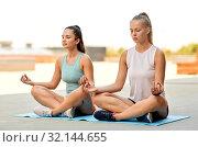 Купить «women doing yoga and meditating in lotus pose», фото № 32144655, снято 28 июля 2019 г. (c) Syda Productions / Фотобанк Лори