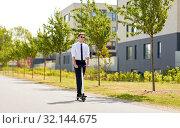 Купить «young businessman riding electric scooter outdoors», фото № 32144675, снято 1 августа 2019 г. (c) Syda Productions / Фотобанк Лори