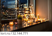 candles burning on window sill with garland lights. Стоковое фото, фотограф Syda Productions / Фотобанк Лори