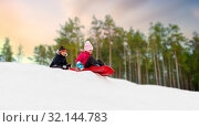 Купить «happy kids sliding on sleds down hill in winter», фото № 32144783, снято 10 февраля 2018 г. (c) Syda Productions / Фотобанк Лори